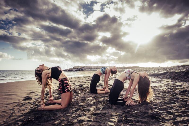 Bloccaggio scenico con tre giovani belle signore dei modelli che fanno allenamento dei pilates e di yoga alla spiaggia sulla sabb immagine stock libera da diritti