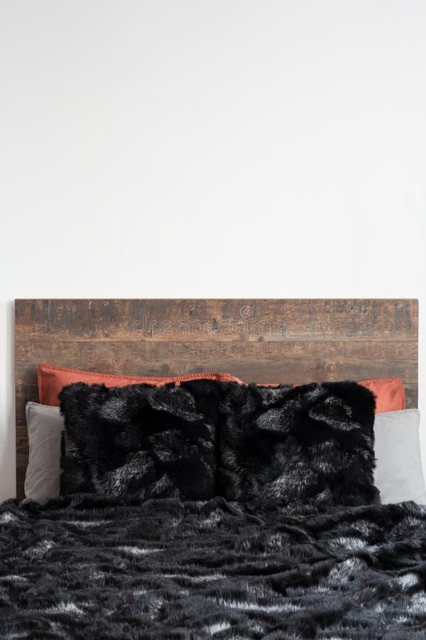 Bloccaggio vicino della coperta simile a pelliccia nera sul letto di legno fotografia stock libera da diritti