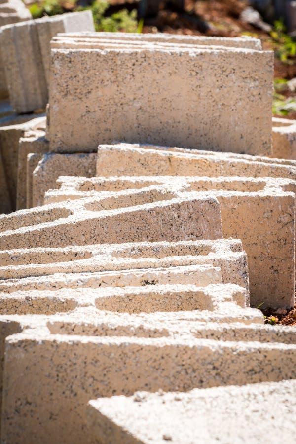Blocchetti di calcestruzzo del cemento sulla terra sul cantiere immagini stock