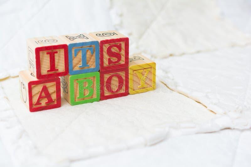 Blocchetti di legno di alfabeto sull'ortografia della trapunta sua un ragazzo inclinato immagini stock
