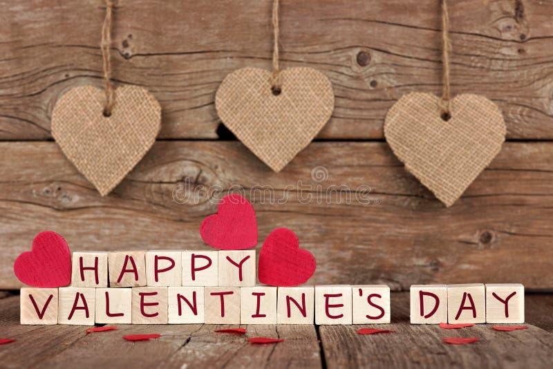 Blocchetti di legno felici di giorno di biglietti di S. Valentino con la decorazione del cuore su legno immagine stock libera da diritti