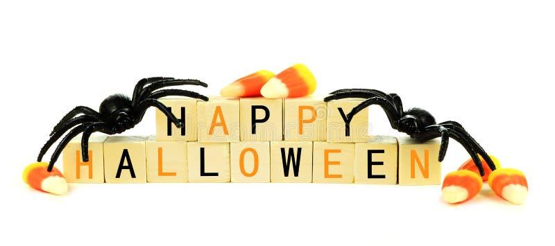 Blocchetti di legno felici di Halloween con la caramella e la decorazione sopra bianco fotografia stock libera da diritti