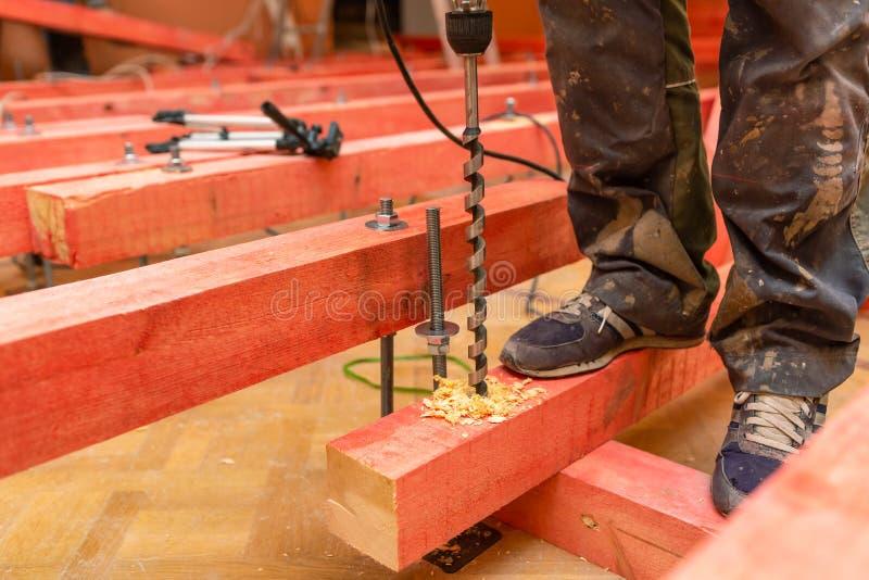 Blocchetti di legno di perforazione del muratore dal perforatore con il pezzo alesato lungo in appartamento che è sotto il constr immagine stock libera da diritti