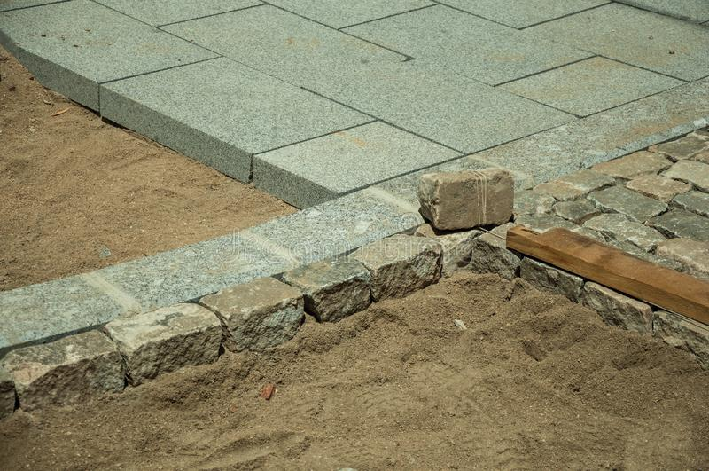 Blocchetti di pietra dei pavè chesono messi in un cantiere fotografia stock libera da diritti