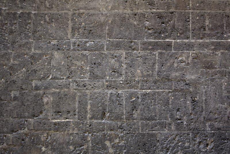 Blocchetti grigi di calcestruzzo di struttura della vecchia parete con le forme interessanti immagini stock