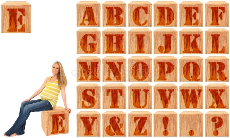 Blocchetti incisi legno di alfabeto con la donna incinta fotografie stock libere da diritti