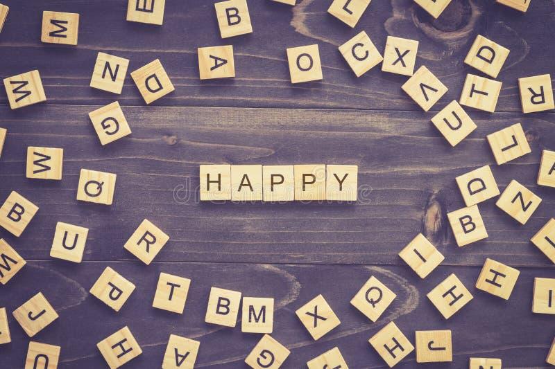 Blocchetto di legno di parola felice sulla tavola per il concetto di affari fotografie stock