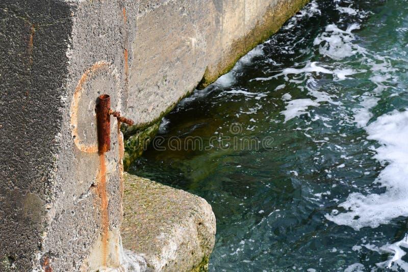 Blocchi in calcestruzzo stagionati del pilastro con vecchia costruzione arrugginita fotografia stock libera da diritti