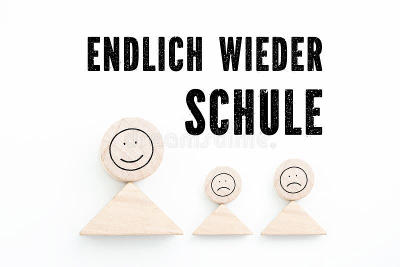 """Blocchi che simbolizzano genitore con i bambini e la frase """"di nuovo a scuola, infine """"in tedesco fotografia stock"""