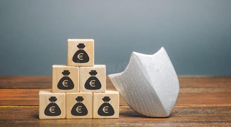 Blocchi di legno con denaro e protezione Concetto di sicurezza monetaria, depositi garantiti Protezione dei diritti dei clienti fotografie stock libere da diritti