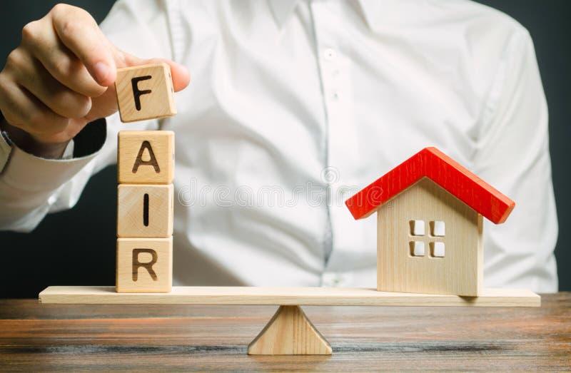 Blocchi di legno con la fiera di parola e una casa di legno Valore giusto del bene immobile e dell'alloggio Valutazione della pro immagine stock libera da diritti