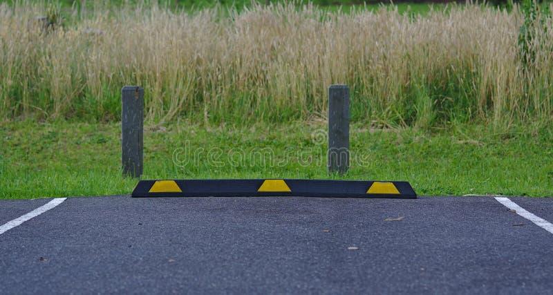 Blocco di parcheggio di gomma nei colori neri e gialli fotografie stock