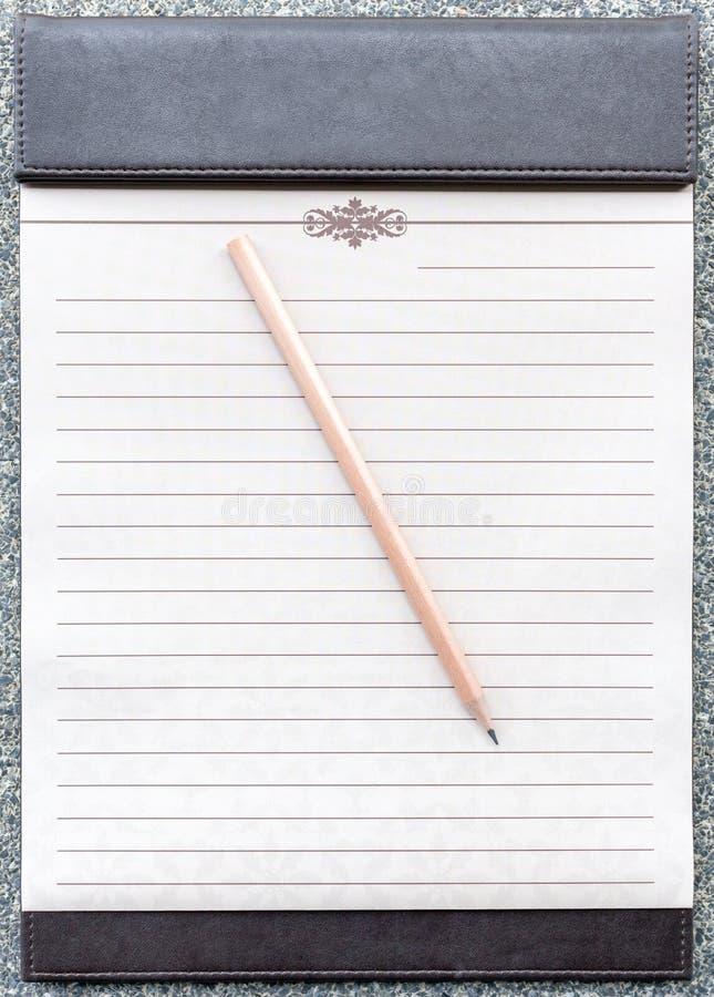 Blocco note in bianco con la matita sulla lavagna per appunti marrone fotografia stock