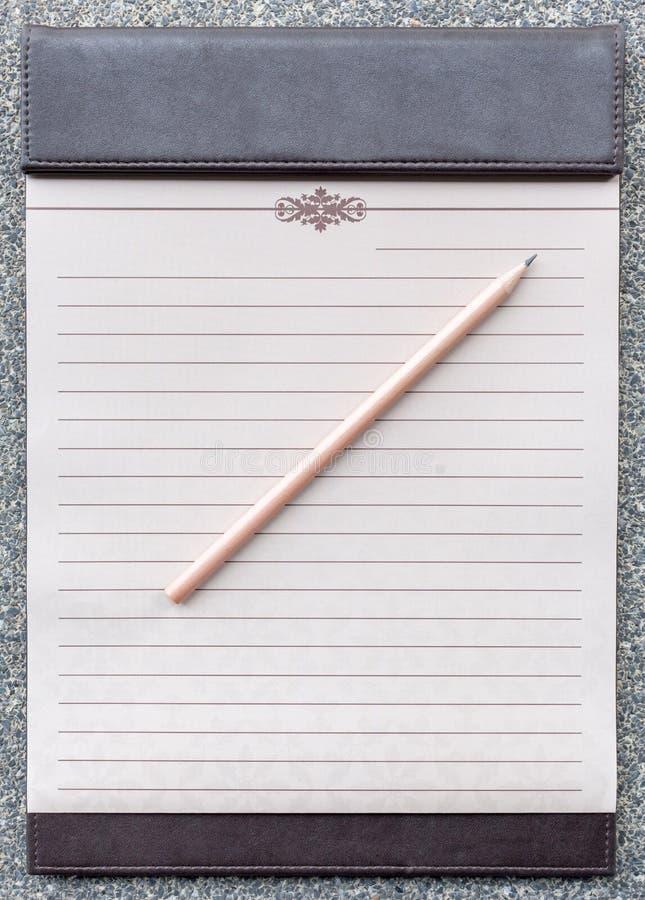 Blocco note in bianco con la matita sulla lavagna per appunti marrone fotografia stock libera da diritti