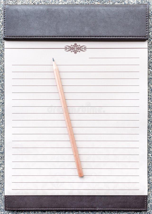 Blocco note in bianco con la matita sulla lavagna per appunti marrone fotografie stock libere da diritti