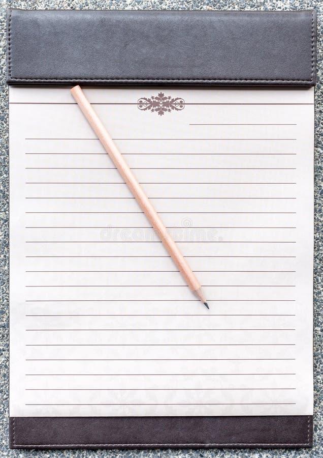 Blocco note in bianco con la matita sulla lavagna per appunti marrone immagine stock libera da diritti