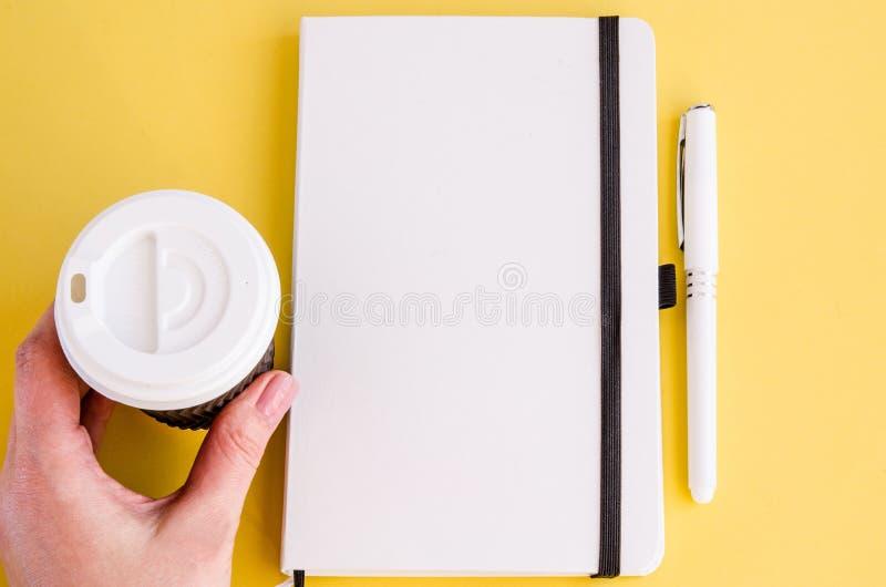 Blocco note bianco, penna, tazza di caffè della carta in una mano femminile fotografia stock