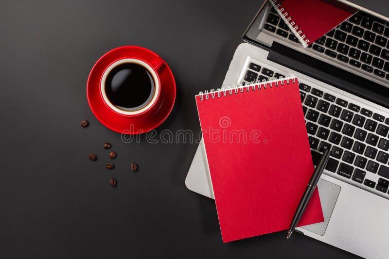 Blocco note in bianco sopra la tazza di caffè e del computer portatile sulla tavola del nero dell'ufficio fotografia stock libera da diritti