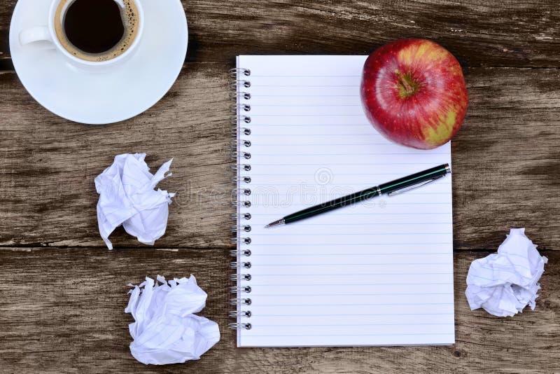 Blocco note con la mela del caffè e carta sgualcita sulla tavola immagini stock libere da diritti