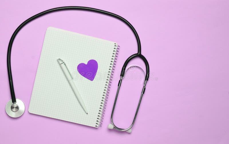 Blocco note con la penna, cuore decorativo, stetoscopio sulla b pastello rosa immagine stock libera da diritti