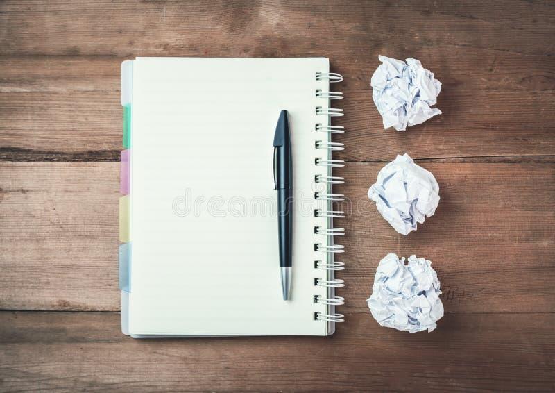 Blocco note con la penna e carte sgualcite su uno scrittorio di legno fotografia stock