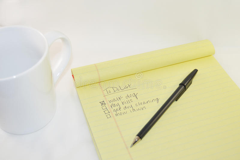 Blocco note con la tazza di caffè macchiato e penna a sfera nera su un fondo bianco fotografie stock