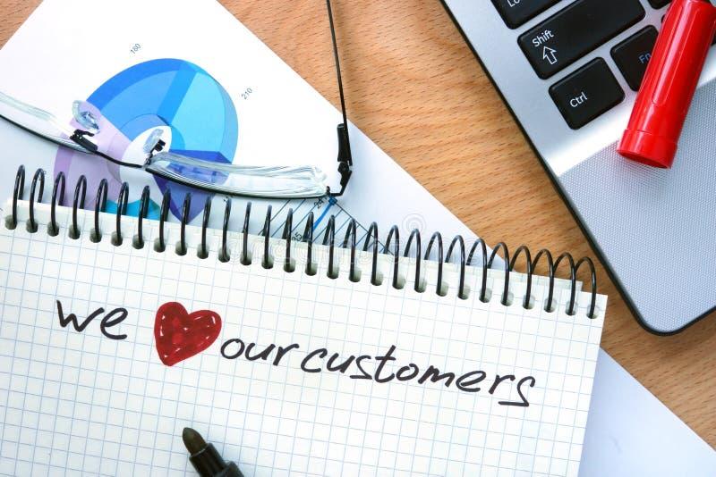 Blocco note con le parole amiamo i nostri clienti immagini stock libere da diritti