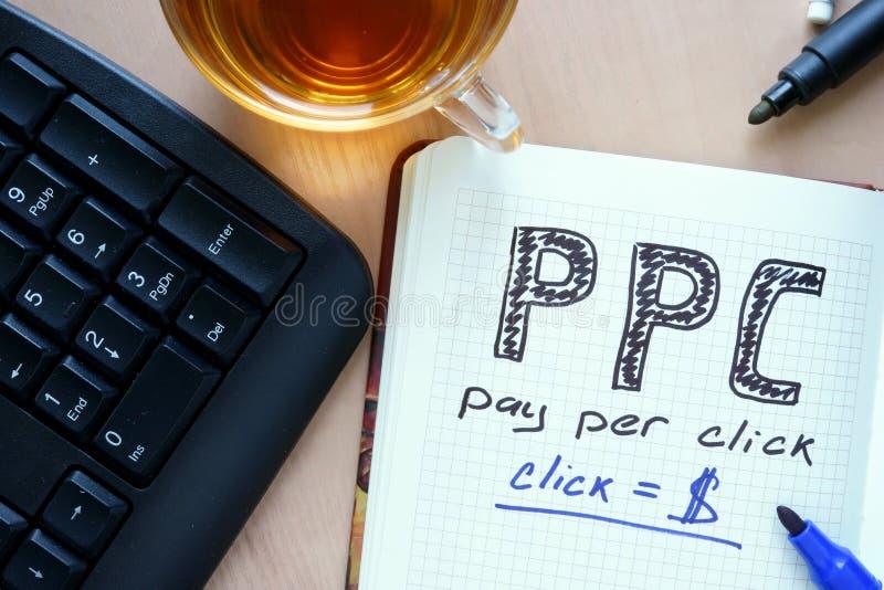 Blocco note con paga di parola PPC per concetto di clic immagini stock