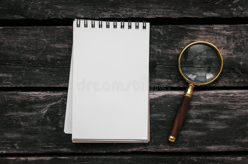Blocco note della pagina in bianco e della lente d'ingrandimento fotografia stock libera da diritti