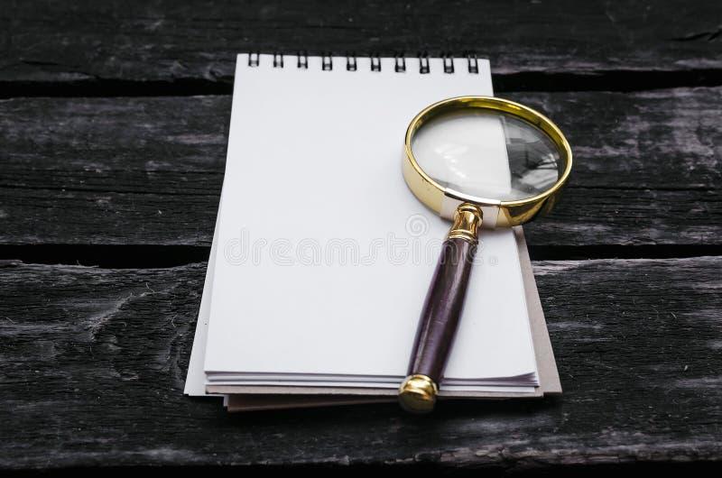 Blocco note della pagina in bianco e della lente d'ingrandimento immagini stock libere da diritti