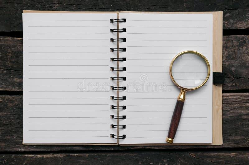 Blocco note della pagina in bianco e della lente d'ingrandimento immagini stock