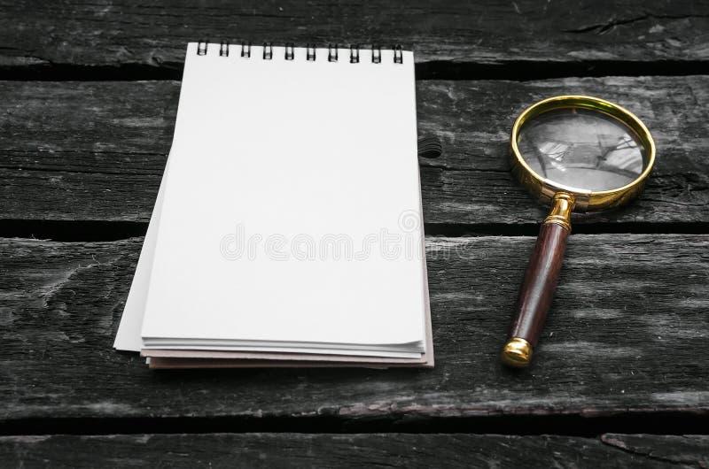 Blocco note della pagina in bianco e della lente d'ingrandimento immagine stock