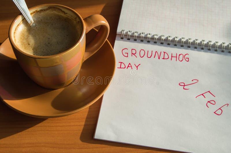 Blocco note di febbraio di giorno della marmotta con la data del 2 febbraio e la tazza di caffè espresso immagine stock libera da diritti