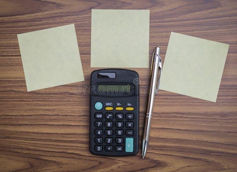 Blocco note e calcolatore in bianco con la penna d'argento su fondo di legno immagine stock libera da diritti