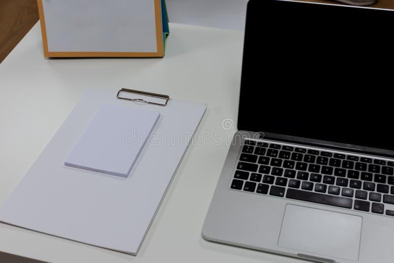 Blocco note e computer portatile sullo scrittorio di legno bianco Vista da sopra con lo spazio della copia nel tono bianco Fondo  immagine stock libera da diritti