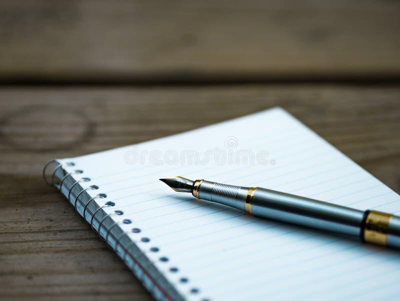 Blocco note e penna sulla scrivania fotografie stock libere da diritti