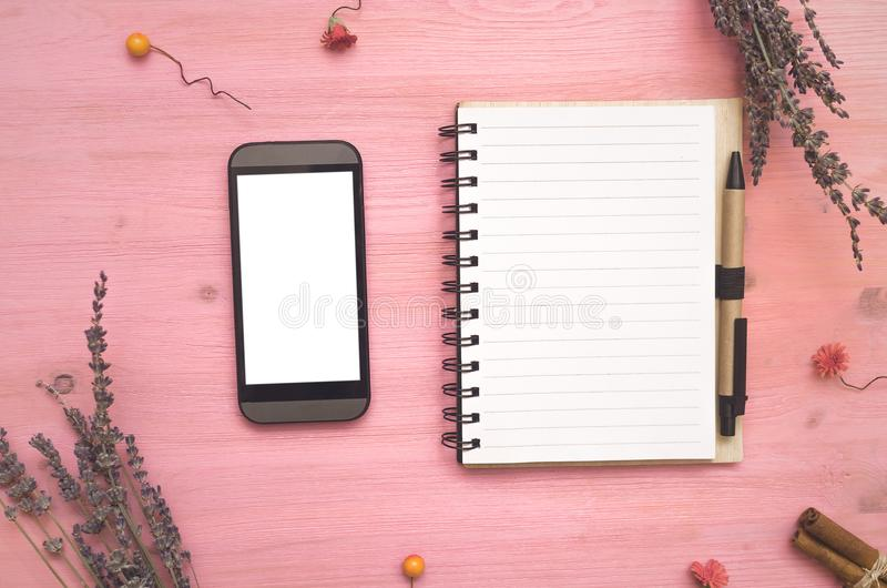 Blocco note e telefono cellulare della pagina della carta in bianco con lo schermo bianco per fare le punte della lista immagini stock libere da diritti