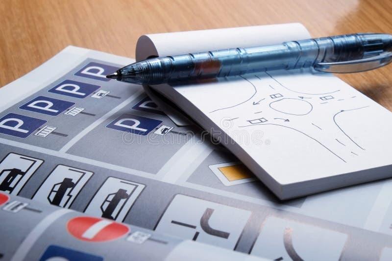 Blocco note, libro di codice stradale e penna su una tavola dello scrittorio immagine stock libera da diritti