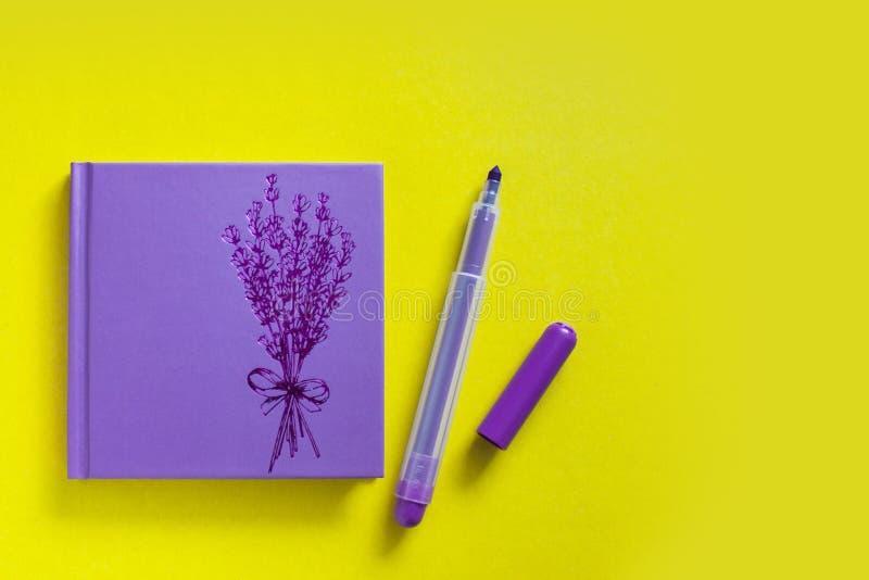 Blocco note lilla con la penna del feltro su fondo giallo fotografie stock