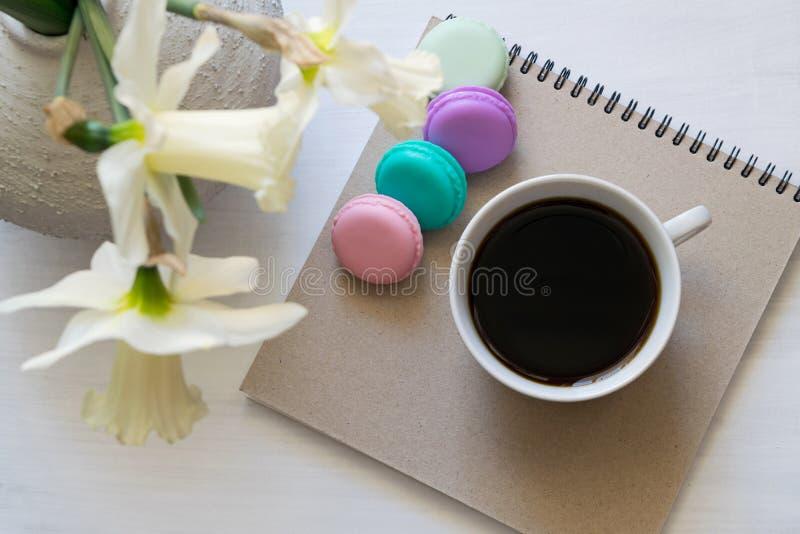 Blocco note, macarons, tazza di caffè e narcisi in un vaso su una tavola bianca Posto di lavoro ispiratore fotografie stock libere da diritti