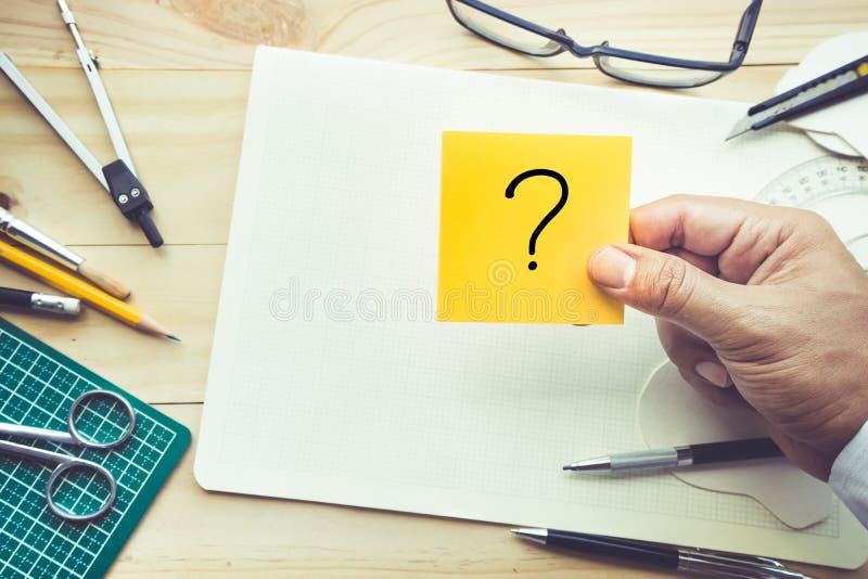 Blocco note maschio della tenuta della mano con i punti interrogativi sulla tavola di lavoro immagine stock libera da diritti