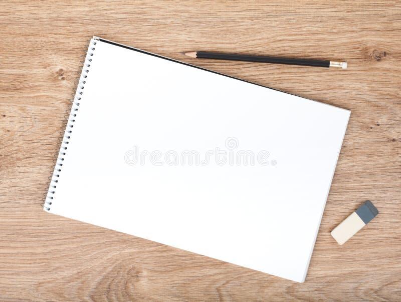 Blocco note, matita e gomma in bianco sulla tavola di legno fotografia stock