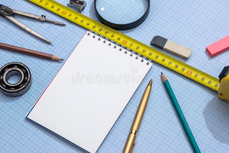 Blocco note, matita, righello e bussola su carta millimetrata immagine stock