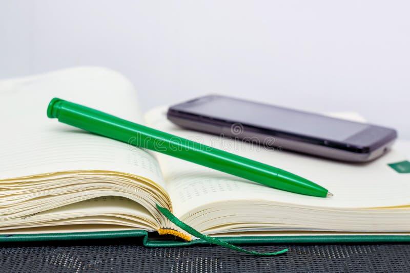 Blocco note, penna e telefono - mezzi di informazioni di registrazione durante fotografie stock libere da diritti