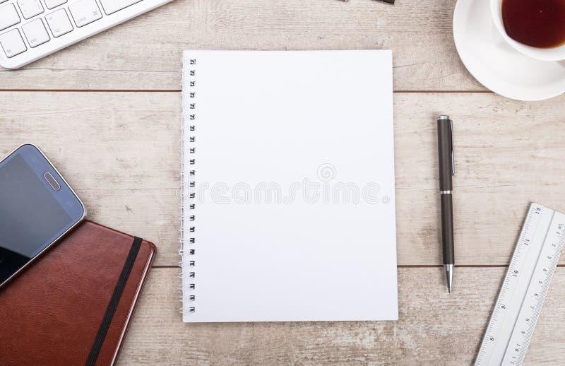Blocco note, penna, tè e smartphone sulla tavola di legno immagine stock