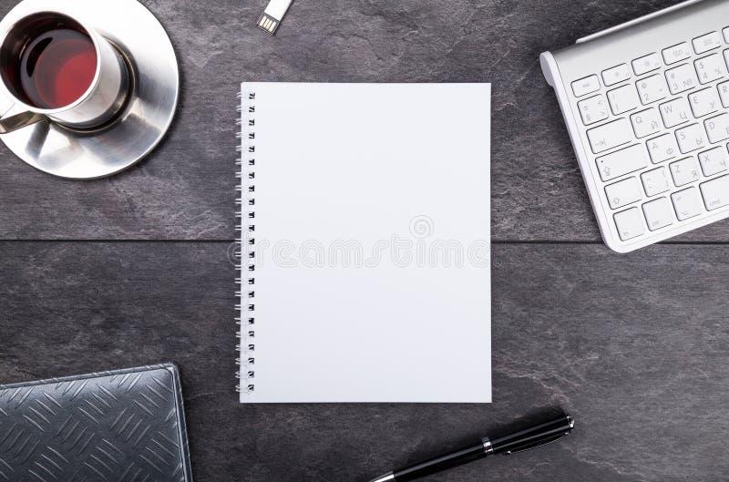 Blocco note, penna, tè e tastiera sulla tavola di pietra fotografia stock libera da diritti