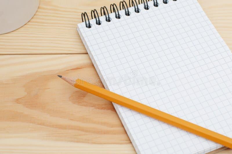 Blocco note a spirale in bianco con la matita che mette su scrittorio di legno Tavola moderna dello scrittorio della casa del pro fotografie stock libere da diritti