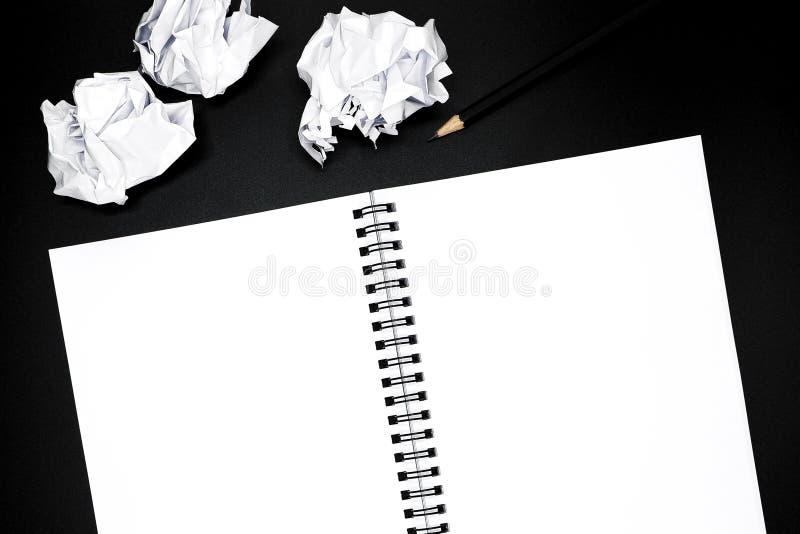 Blocco note a spirale in bianco con la matita nera e le carte sgualcite su fondo nero fotografie stock