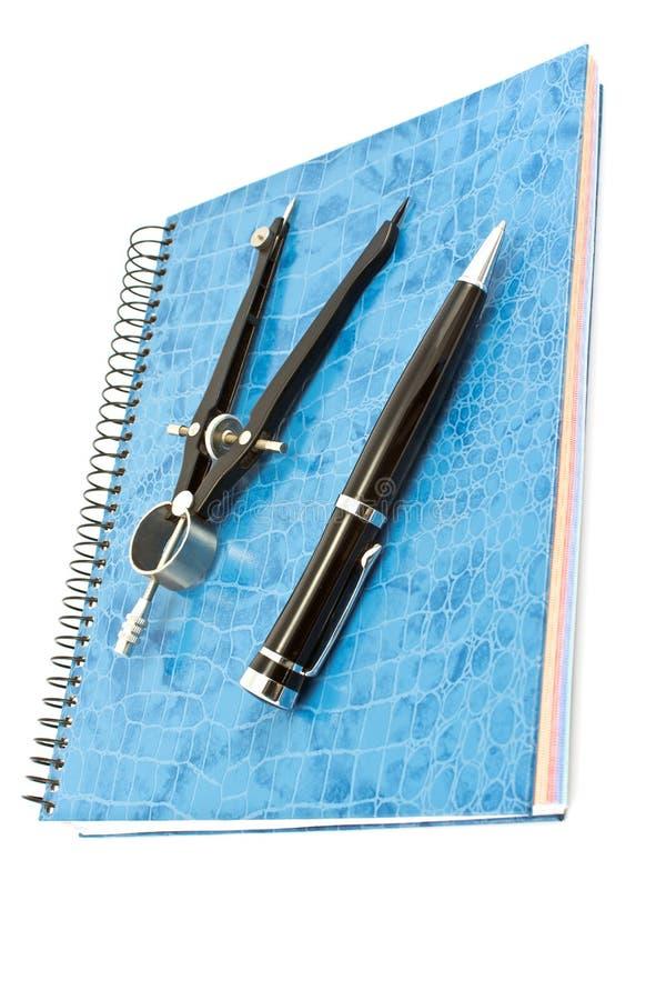 Blocco note a spirale blu con la bussola di disegno e della penna fotografia stock libera da diritti