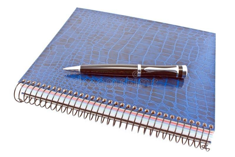 Blocco note a spirale blu con la penna fotografia stock